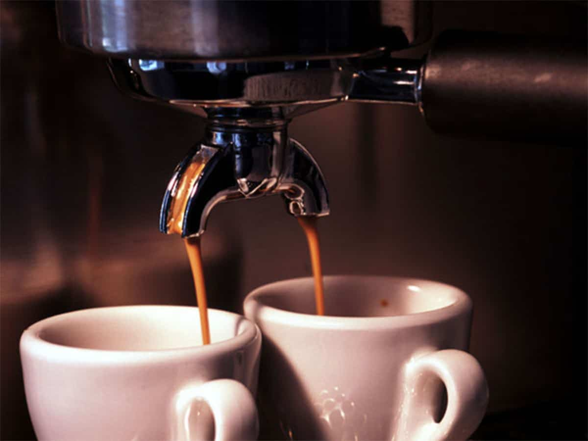 coffee being dripped into two tiny cups