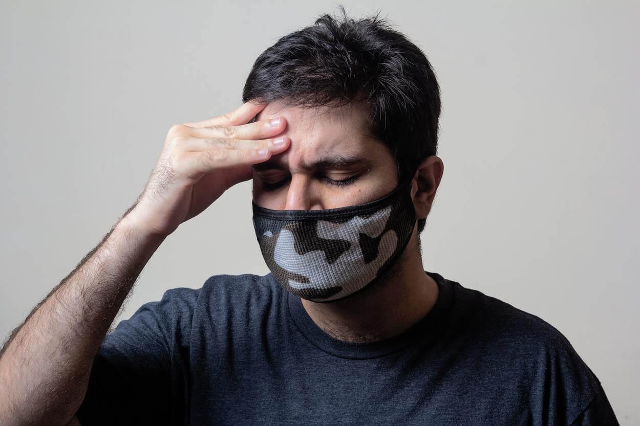 A man hiding face for headache.