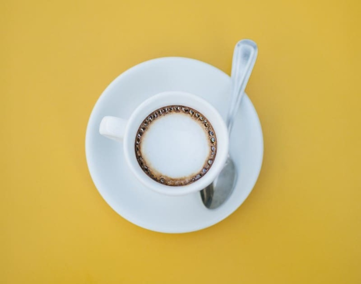 a cup of coffee on a small plate with a spoon