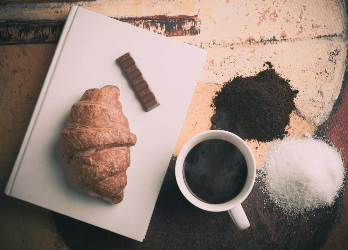 Coffee, sugar, croissant, and a chocolate.