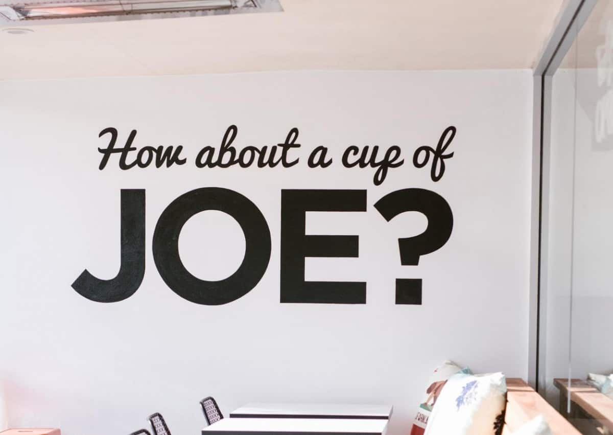 a white wall with the words 'how about a cup of Joe?' on it