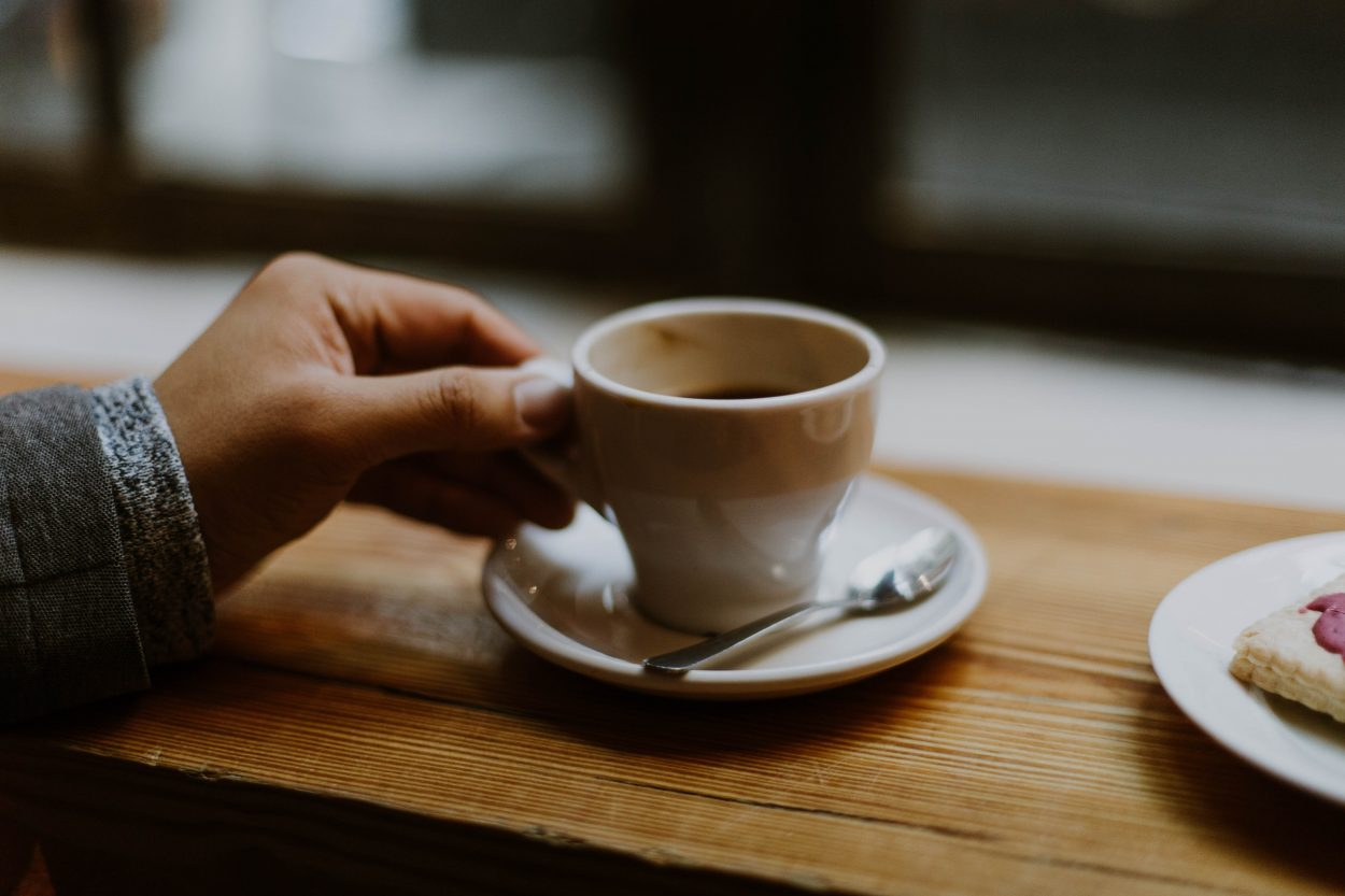 a hand holding a tiny cup of coffee