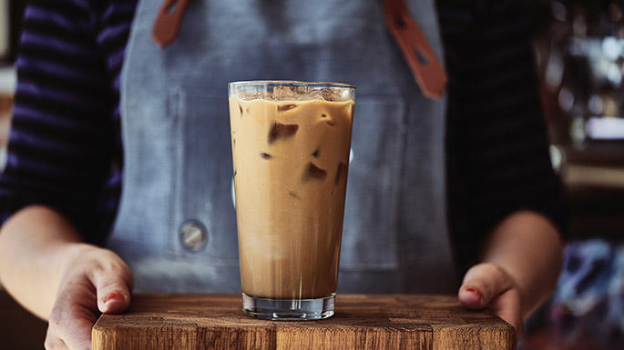 a person serving iced coffee in a glass