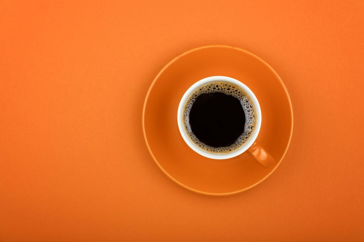 an above view of coffee in an orange cup on an orange plate