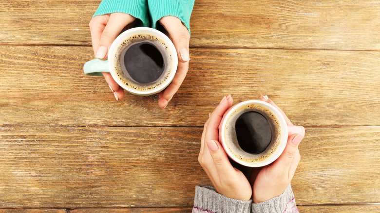 two cups of coffee in two pairs of hands