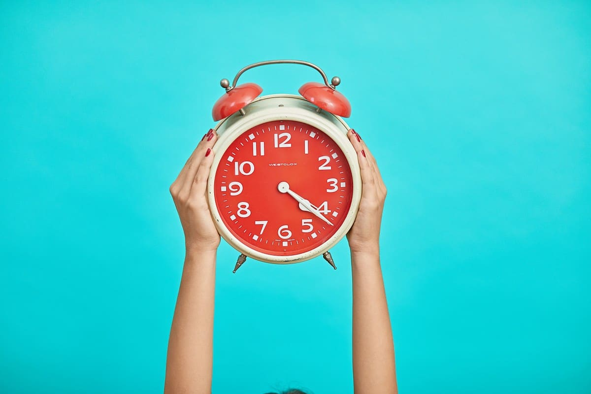 two hands holding up a big alarm clock