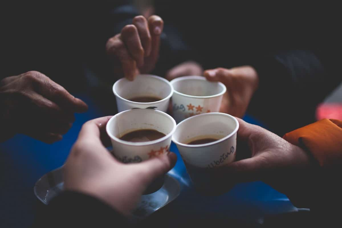 four people toasting to four cups of coffee